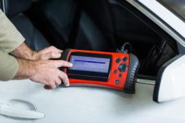 Hands of mechanic using a diagnostic tool in repair garage